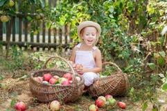 Ein kleines Mädchen, das einen Apfel im Garten isst Lizenzfreie Stockfotografie