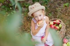Ein kleines Mädchen, das einen Apfel im Garten isst Lizenzfreies Stockfoto