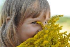 Ein kleines Mädchen, das einen Blumenstrauß des Feldsommers hält, blüht und ihn mit ihren geschlossenen Augen, das riecht Stockfoto