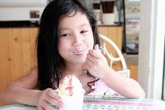 Ein kleines Mädchen, das Eiscreme isst Stockfotos