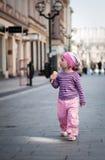 Ein kleines Mädchen, das entlang die Straße mit einem Eis-creame geht Stockbilder