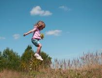 Ein kleines Mädchen, das gegen den Hintergrund des blauen Himmels springt Stockfotografie
