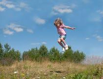 Ein kleines Mädchen, das gegen den Hintergrund des blauen Himmels springt Lizenzfreie Stockfotos
