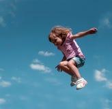 Ein kleines Mädchen, das gegen den Hintergrund des blauen Himmels springt Stockbild