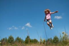 Ein kleines Mädchen, das gegen den Hintergrund des blauen Himmels springt Lizenzfreie Stockfotografie