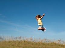 Ein kleines Mädchen, das gegen den Hintergrund des blauen Himmels springt Stockfotos