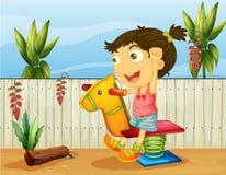 Ein kleines Mädchen, das innerhalb des Zauns spielt lizenzfreie abbildung