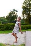 Ein kleines Mädchen, das lustige Gesichter auf einem Gras in einem schönen grünen Park tanzt und macht Lizenzfreie Stockfotografie