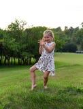 Ein kleines Mädchen, das lustige Gesichter auf einem Gras in einem schönen grünen Park tanzt und macht Stockfoto