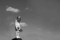 Ein kleines Mädchen, das mit ihrem Kopf unten gegen die breiten Himmelhintergründe steht Stockfotografie