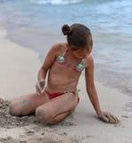 Ein kleines Mädchen, das mit Sand auf dem Strand spielt Lizenzfreies Stockbild