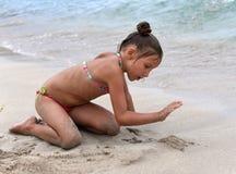 Ein kleines Mädchen, das mit Sand auf dem Strand spielt Lizenzfreies Stockfoto