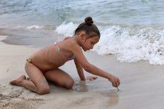 Ein kleines Mädchen, das mit Sand auf dem Strand spielt Stockfoto