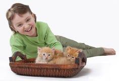 Ein kleines Mädchen, das mit Schätzchenkatze spielt Lizenzfreie Stockfotografie