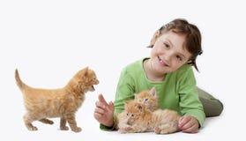 Ein kleines Mädchen, das mit Schätzchenkatze spielt Stockbild