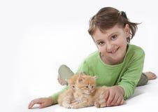 Ein kleines Mädchen, das mit Schätzchenkatze spielt Stockfotos