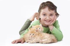 Ein kleines Mädchen, das mit Schätzchenkatzen spielt Lizenzfreie Stockfotografie