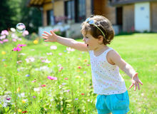 Ein kleines Mädchen, das mit Seifenblasen spielt Lizenzfreie Stockbilder