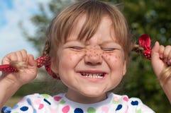 Ein kleines Mädchen, das Pippi Longstocking mit ihren Augen darstellt, schloss und Gesichter, das macht Stockbild