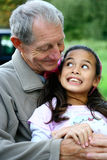 Ein kleines Mädchen, das Spaß mit ihrem Großvater hat Lizenzfreie Stockfotos