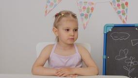 Ein kleines Mädchen, das am Tisch im Kinderzimmer sorgfältig nach vorn schaut sitzt stock footage