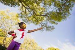 Ein kleines Mädchen, das vortäuscht, mit Superheldkostüm zu fliegen Lizenzfreie Stockfotografie