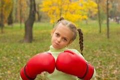 Ein kleines Mädchen in den enormen Boxhandschuhen macht ein schlechtes Gesicht Stockfotos