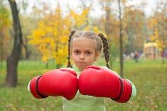 Ein kleines Mädchen in den enormen Boxhandschuhen macht ein schlechtes Gesicht Stockfoto