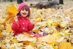 Ein kleines Mädchen in den gelben Blättern Stockfoto