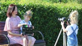Ein kleines Mädchen in den Kopfhörern mit einer Kamera schießt den Plan stock video footage