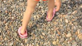 Ein kleines Mädchen in den korallenroten Pantoffeln ist auf den Felsen auf dem Strand