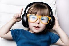 Ein kleines Mädchen in den orange Hippie-Gläsern hört Musik auf Kopfhörern im Lehnsessel des Hauses Lizenzfreie Stockbilder