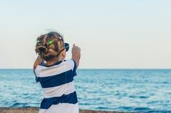 Ein kleines Mädchen in der Sonnenbrille stellt auf etwas mit ihrer Hand dar lizenzfreie stockfotografie