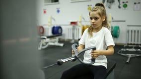 Ein kleines Mädchen in der Turnhalle trainiert auf der Maschine stock footage