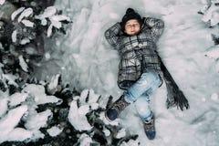 Ein kleines Mädchen in der Winterkleidung, die auf einer schneebedeckten Wieseneinfassung liegt stockfotografie