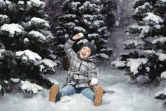 Ein kleines Mädchen in der Winterkleidung, die mit Schnee auf einer schneebedeckten Wiese umgeben durch Tannenbäume spielt Weihna stockfotografie