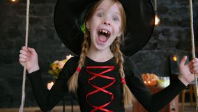 Ein kleines Mädchen, eine Hexe, Fahrt auf ein Schwingen auf Halloween stock video
