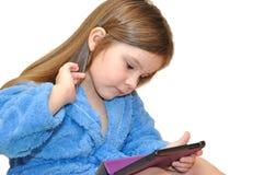 Ein kleines Mädchen in einem Bademantel, nach einem Bad, mit einer Tablette Lizenzfreie Stockbilder