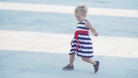 Ein kleines Mädchen in einem Kleid in einem Streifen läuft langsam herum in einen Kreis stock video