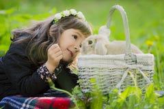 Ein kleines Mädchen in einem Kranz beobachtet ein Kaninchen in einem Korb bei Sonnenuntergang in einem Park Stockbild