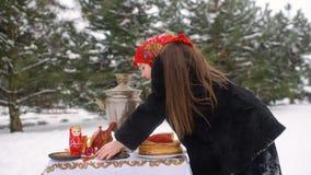 Ein kleines Mädchen in einem Pelzmantel und in einem Schal in der russischen Art setzt an eine festliche Tabelle eine Platte mit  stock video