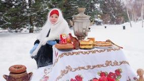 Ein kleines Mädchen in einem Pelzmantel und in einem Schal in der russischen Art sitzt an einem festlichen Tisch und spielt ein r stock video