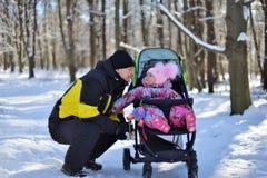 Ein kleines Mädchen in einem rosa Hut und Overall für einen Weg im Wald auf einem Winter schneebedeckt stockbilder