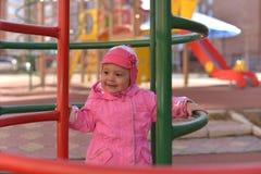 Ein kleines Mädchen in einem roten Hut, der auf dem Spielplatz im Herbst spielt stockfotografie