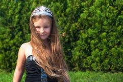 Ein kleines Mädchen in einem schwarzen Kleid mit einer Krone, langes Haar, auf einem grünen Hintergrund, ein Tag, ein Wind, eine  Lizenzfreies Stockbild