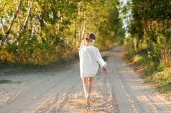 Ein kleines Mädchen in einem weißen traditionellen Ñ- hemise, das in eine szenische Frühherbstlandschaft läuft Stockbilder