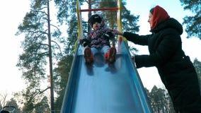 Ein kleines Mädchen in einer bunten Jacke zieht unten von einem mehrfarbigen Dia mithilfe ihres Parks der Mutter im Frühjahr um stock footage
