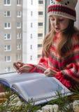 Ein kleines Mädchen in einer gestrickten Strickjacke, die auf einem Fensterbrett sitzt und ein Buch liest lizenzfreie stockbilder