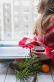 Ein kleines Mädchen in einer gestrickten Strickjacke, die auf einem Fensterbrett sitzt und ein Buch liest Stockfotografie