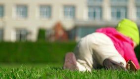 Ein kleines Mädchen in einer rosa Strickjacke und grünen in einem Hutschleichen auf dem Gras stock video